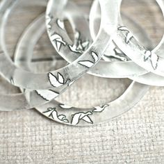 One glass Geese bangle handcrafted from a repurposed Grey Goose Vodka bottle. This bracelet features the portion of the vodka bottle with the white geese. #revetro #jewelry #ecofashion