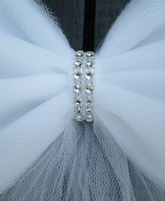 Tulle Bling Bow, Available in white or ivory. - Custom Made - Color: White or Ivory - Size: Approximately 11 wide x 20 tails - Handcrafted with 6 wide tulle ribbon - Two rows of silver bling ribbon on center band - 30 long matching thin satin ribbon ties attached on back Bling ribbon features faceted indentations that simulate rhinestones, no stones. Each item is handmade and may slightly vary. Colors may slightly vary due to photography lighting and your monitor setting.  Visit our website…