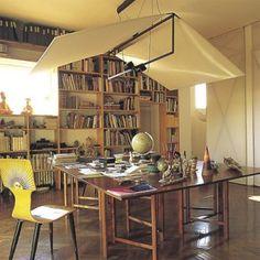 """Le bureau est éclairé par une suspension en toile éclaire 2 tables juxtaposées de Bruno Mathsson (1930),  la chaise """"Sun"""" de Piero Fornasetti (1955) et une bibliothèque qui occupe un mur entier."""
