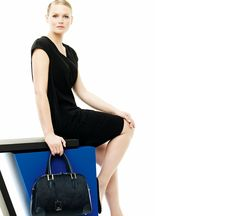 Marina Rinaldi - Collection for Curvy women  Black cap-sleeved dress in stretch jersey worn with black suede pumps and navy blue horsehair bag.
