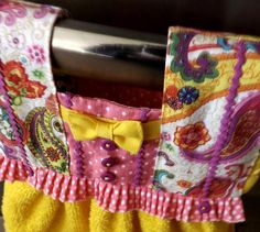 This colorful bright yellow and pink oven dress makes a unique housewarming or kitchen shower gift that is as practical as it is decorative. Ive pieced together pink polka dot cotton and a retro paisley cotton print accented with magenta baby rick rack, magenta buttons, and pink polka dot pre-gathered trim ruffling for the top. The towel skirt is bright lemon yellow cotton terry. Ive sewn the seams and topstitching by hand, my favorite way to sew. The top is fully lined in the same patchwork…