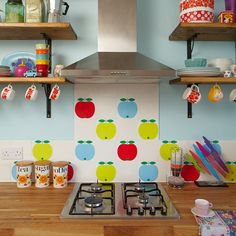 Small kitchen with blue walls, apple splashback tiles, open shelving and under-shelf cup hooks
