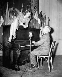 A sultry Lauren Bacall sitting atop an upright piano while President Harry Truman plays