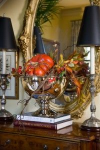 5227 Nell Hill's shop's side table display for fall!!! Bebe'!!! Includes books, a silver pedestal bowl filled with a pumpkin and small bouquet of dried flowers, and candlesticks all reflected in an elegant goldleafed framed formal room mirror!!!