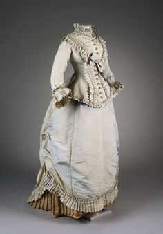 1876 bodice and skirt gray and yellow (previously pale blue, now faded) Elaborate pleated trimmings and lavish dust ruffle. Polonaise draping to the back has come down.