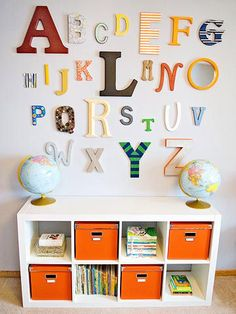 """World's best shower idea! Instead of playing typical baby-shower games, Katie's guests decorated letters for Eli's bedroom wall, to hang above his IKEA Expedit bookcase. In addition to the papier-m?ch? and wooden letters from JoAnn Fabrics, the party hostess gave guests acrylic craft paint, craft paper, fabric, buttons, and twine. """"I love that his room has art handcrafted by my best friends,"""" Katie says."""