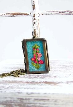 Embroidered Hollyhocks Locket Necklace   Finally, a bouquet that doesn't require even the most rudiment...   Necklaces