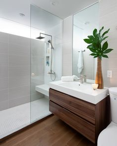 Example of a minimalist gray tile bathroom design in Toronto with an integrated sink, flat-panel cabinets and dark wood cabinets #bathroom #modern