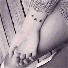 Pequeño tatuaje en la muñeca de tres pájaros volando.