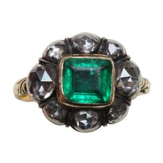 An elegant ring with 8 rose cut diamonds set in silver and in the center an emerald set in gold, a floral engraved shank with black enamel decorations at the back, European, 17th century.