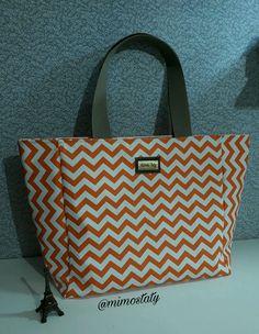 Bolsa feita com material sintético impermeável, pvc, forrada com cetim dublado, bolso interno, fechamento com botão de imã, tamanho 50cm de largura por 32.cm altura.