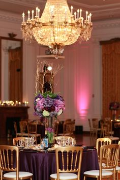 Pink lighting with purple table setting and gold versaille chairs.