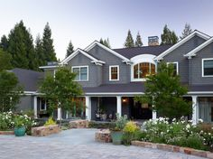 This Shingle Style-inspired lodge features a wraparound covered porch providing distinct views to the landscape. Working closely with the architect and owners, we designed an estate landscape that realized this family's vision for rugged charm that both recalls their Southern roots and draws upon the horticultural richness of the Bay Area.