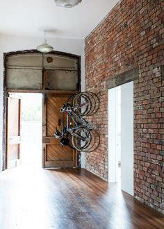 Exposed Brick, a big door and bikes on a wall. It would be nice to have this much space!