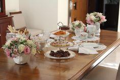 Mesa posta com muitas flores para um chá da tarde com as amigas, prato de doces de cristal da Wolff, porcelana branca, jogo de café Vista Alegre.