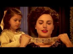 """Scene from """"Woman in Gold"""" - young Maria places Adele's favorite necklace about her aunt's neck"""