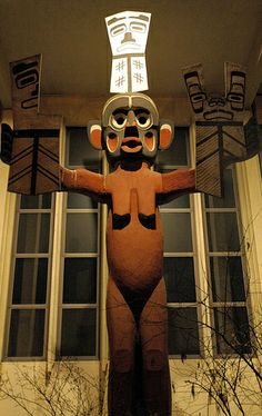 """Tsonoqua, Wild woman of the woods, may she bring everyone wealth, symbolic """"copper"""" in each hand, that they are broken makes them more valuable.  """"welcoming post""""or house post, totemic design, University of Washington, Seattle, Washington, USA"""