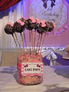 Cake Pops en chocolate cafe con grageas y moñito en pastillaje. Foto tomada de Mily's Cupcakes (Argentina)