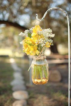 Wild flowers in mason jars on shepherd's hooks, river rocks outlining the aisle