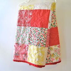 Patchwork baby quilt in reds, pinks, and yellows.