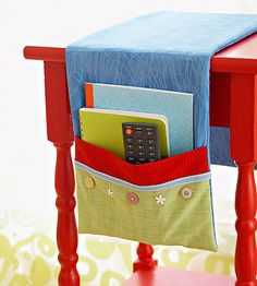If you need storage but your accent tables don't provide the drawer or shelf space you want, get creative with a table runner. Sew on a pretty fabric pocket that hangs over the side of the table to keep handy a few necessities such as a notebook and remote. For a no-sew option, attach the pocket with fusible seam tape or fabric glue.