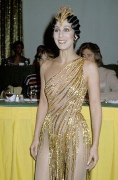 Cher at the 1978 Disco Convention Banquet in New York City.  She looked more like Tinkerbell at an ice-skating rink in her revealing one-shoulder gold sequined dress by designer Bob Mackie
