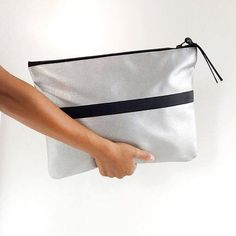 Impress with the in-vogue silver metallic oversized clutch bag, made of Italian vegan animal-friendy leather, durable and easy to clean. This hand carry soft clutch bag features grey body backing with one zip pocket perfect to carry you laptop, macbook air and i pad. Metal zip closure. Fully lined with one inner pocket. It is the perfect bag to wear for a cocktail party or for every day wear. Dimentions: 14.5x10in (37x25.5cm)  Label: Pitti Vintage Handmade in Italy One handmade dust bag is…