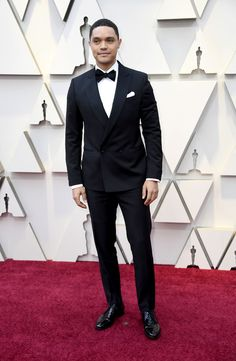 "The words ""classic done and donned well"" are the first ones that came to mind after peeking Trevor Noah's Oscar red carpet look: a debonair double-breasted black Ferragamo tux. Joanne Tucker, Chelsea Peretti, Chris Evans Tumblr, Mahershala Ali, Trevor Noah, Mark Ronson, Best Dressed Man, Tuxedo Dress, Pharrell Williams"