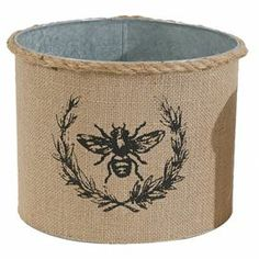 """Perfect for stowing cotton balls in your master bath or wrapped candies on the kitchen counter, this burlap-wrapped tin canister charms with a bee and laurel leaf detail.  Product: CanisterConstruction Material: Tin and burlapColor: Brown Features: Bee motifDimensions: 7"""" H x 9.3"""" Diameter"""