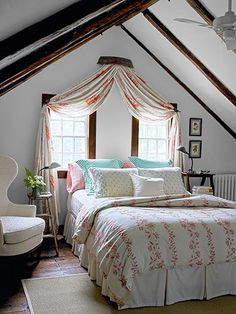 "Clever idea for a window treatment when you have to put the bed there. Plays up the vaulted ceiling too as well as giving you that ""crown"" look that's so attractive. To me, an arched upholstered headboard would finish up the look.Just put blinds in the windows for privacy & sun control."