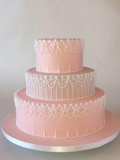 This cake is a made with Fondarific white chocolate fondant.  The base fondant is a blush peachy pink.  The royal drop strings and accents are made with white royal icing.