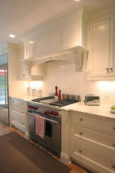 Great range hood, not too curvy and blends with cabinetry. Minus the fluted corbels though...