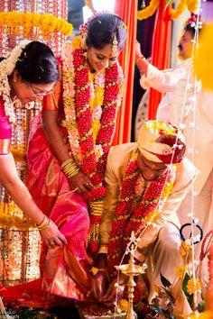 Groom putting on the traditional toe ring for the bride, at a lovely South Indian wedding