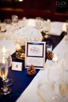 Ivory tables with navy table runners.... love the centerpieces and flowers with the pinecones!