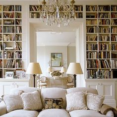 [Symmetry in white fluffly pillows, double cream-colored lamps and large wall-to-ceiling bookshelves.] white library