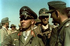 """Field Marshal Erwin Rommel surrounded by his troops in Africa; Major Günther Schrivenbach is right behind Rommel holding a pair of binoculars. Rommel remained a """"soldiers' soldier"""" to the very end preferring constant contact with the troops under his command at all levels."""