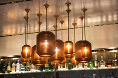 Michael Young's solid brass Bramah pendant lights for Hong Kong brand EOQ hang in clusters along the bar's walkway. Photography courtesy of Hilton.