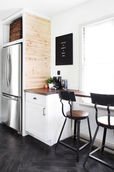 Adorable eat in nook with bar stools in a black and white kitchen remodel. Long grey herringbone tile for the floor, natural wood plank wall framing the fridge. Stainless steel appliances. So charming for a small space.
