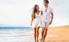 Beach couple walking on romantic travel honeymoon vacation summer holidays romance. young happy lovers, asian women and caucasian men holding hands