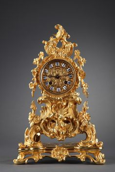 A small mantel clock in French rocaille style decorated with a rich gilt and chiselled bronze decoration: foliage, scrolls, shells, gadrooned leaves, garlands of flowers and acanthus leaves.
