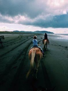 riding horses on the beach. Foggy, gloomy day