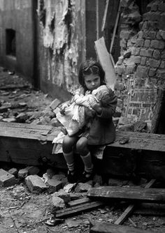 A little girl holds her doll in front of her bombed out home, London, ca. 1940's. ☀