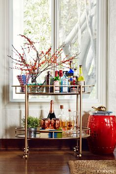 Gold bar cart with large red branches and fully stocked liquor