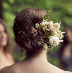 This bride's thick, dark blonde hair is styled in a cluster of low buns. Flowers are added as a final touch to this romantic wedding updo.