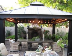 Gravel patio, wicker chairs. Raised flower beds with fireplace.