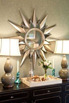 Gold sunburst mirror and grey lamps.