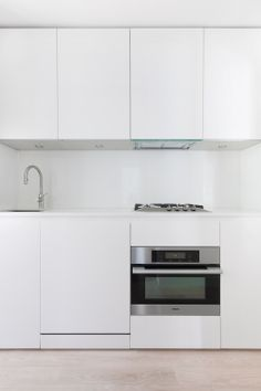 """54 square feet kitchen in Union Square, NYC. GLAM Kitchen: matte white smooth lacquer cabinets including a dishwasher, a 24"""" Miele oven, a four burner Miele cooktop, and a custom hood by Falmec."""