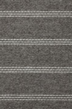 Heywood in Dark Gray - Undyed Dark Gray and Thin Felted Natural - Customizable with all yarn colors. Heywood combines the hand-stitched look of a bespoke suit with a toothy weave structure to create an irresistible textural effect. A flatweave rug made from undyed heathered and felted wools, Heywood is available in 3 rich colorways: Dark Gray, Chocolate and Jade. John J. Heywood established the Heywood Narrow Fabric Company on Portland Street in Fall River in 1890.