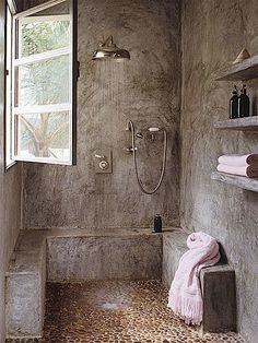 Tan Pebble tile shower pan in beautiful natural bathroom