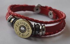 Remington 12 gauge shotgun shell bracelet. Red Leather. Comes with (1) Remington Brass & (1) Nickel Finish Bullet Rim,(1) Bracelet. Mounted to each shell is a Swarovski Crystal. Adjustable from approx. 7 1/2 to 8 1/4 Made from a used fired shotgun shell rim. No powder or active